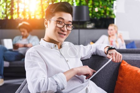 young asian businessman in eyeglasses with digital tablet at modern coworking office
