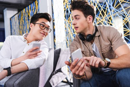 multiethnic businessmen showing smartphones to each other at modern coworking office