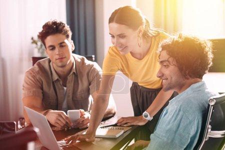 Foto de Sonriendo empresaria usando laptop mientras dos hombres de negocios viendo en pantalla en la oficina moderna - Imagen libre de derechos