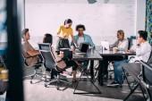 """Постер, картина, фотообои """"многонациональное деловых партнеров, имеющих встречи за столом с ноутбуками в современном офисе"""""""