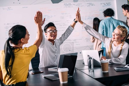 young asian businessman taking high fives to female colleagues at modern office