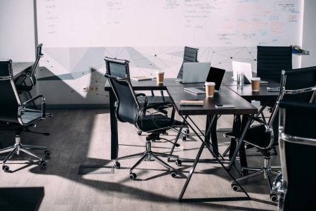 Photo for Front view of interior of modern office with chairs, paper cups of coffee, laptops on table - Royalty Free Image