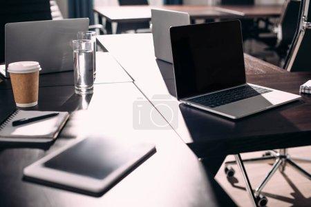 Photo pour Vue rapprochée de tablette numérique, ordinateurs portables, manuel, tasse de café en papier sur la table au bureau moderne - image libre de droit