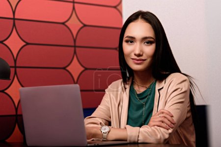 young asian businesswoman sitting at table with laptop at modern office