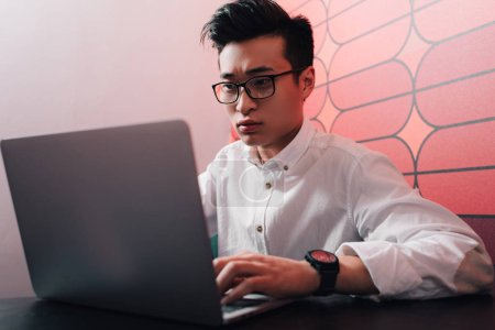 focused young asian businessman working at table with laptop in office