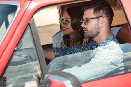 Photo pour Bel homme conduisant voiture avec sa petite amie heureuse - image libre de droit