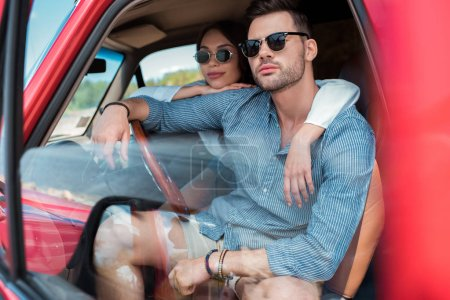Photo for Beautiful couple in sunglasses sitting in car and hugging together - Royalty Free Image