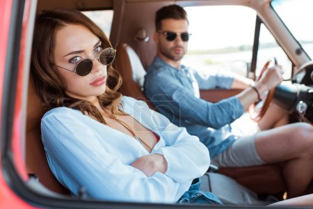 selective focus of beautiful upset woman sitting in car with her boyfriend