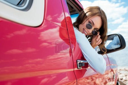 Photo for Beautiful smiling traveler in sunglasses sitting in red car during road trip - Royalty Free Image