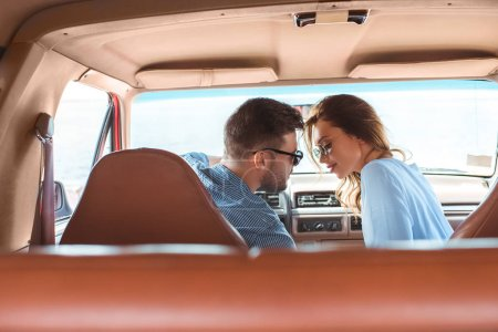 beautiful young couple going to kiss in car