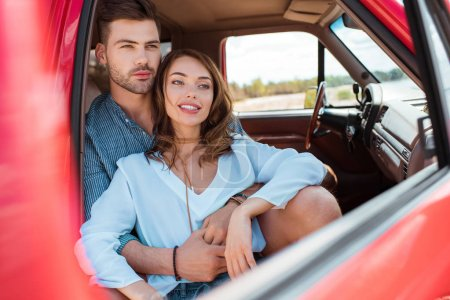 happy young couple of travelers hugging and sitting in car