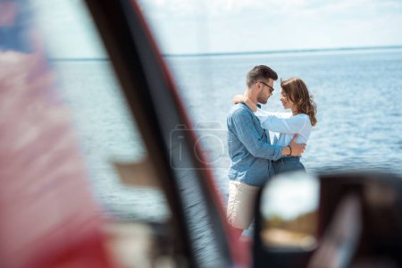 selective focus of car and young couple embracing near sea