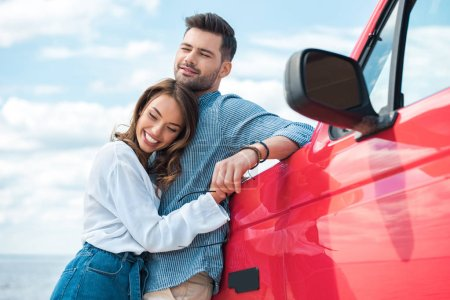Photo for Cheerful young couple hugging near red car - Royalty Free Image