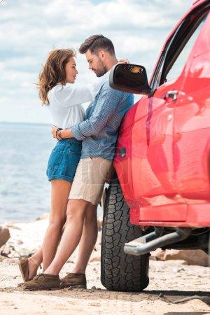 Photo pour Heureux beau couple de voyageurs embrassant près de jeep rouge - image libre de droit
