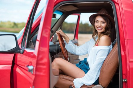 attractive female driver in hat sitting in car during road trip