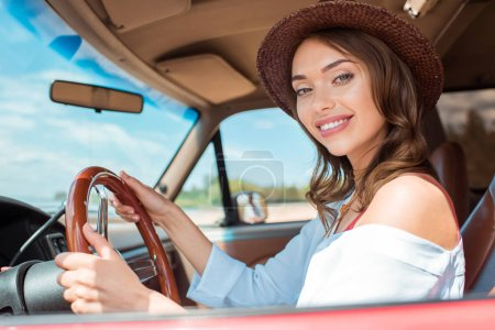attractive smiling woman in hat driving car during road trip