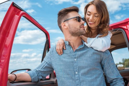 Photo for Smiling beautiful couple hugging near car together - Royalty Free Image