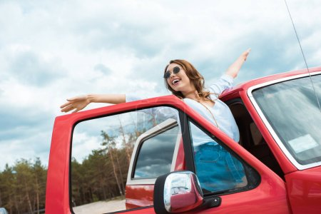 Photo for Excited young woman in sunglasses posing near red car during trip - Royalty Free Image