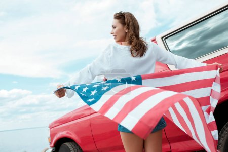 attractive young woman with usa flag standing near red car