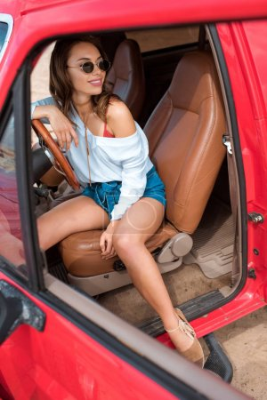 beautiful stylish girl in sunglasses sitting in car during road trip