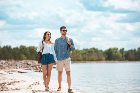happy couple holding hands and walking with backpacks on sea shore