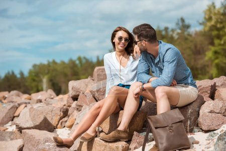 young couple sitting together on rocks outside