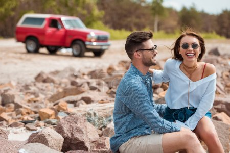 smiling couple sitting on rocks with red jeep on background