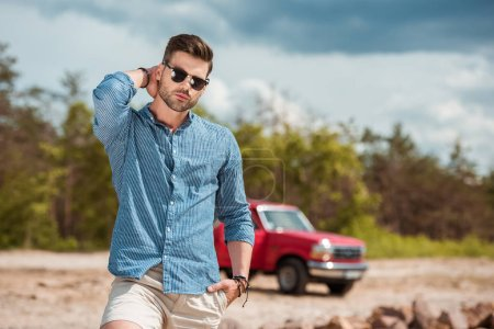 handsome stylish man in sunglasses, red jeep on background