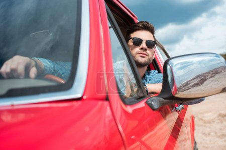 handsome man in sunglasses sitting in red car during road trip