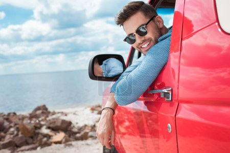 handsome cheerful man in sunglasses sitting in red car during road trip near the sea