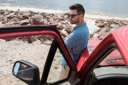 handsome stylish traveler standing at car near the sea during road trip