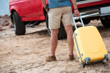 cropped view of man with yellow travel bag going to car