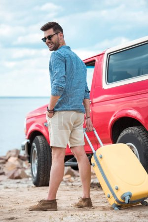 stylish man with travel bag going to red jeep near the sea