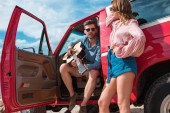 young couple of travelers with acoustic guitar near red car