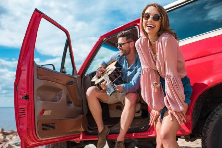 Photo for Young man playing guitar near car with cheerful girlfriend - Royalty Free Image