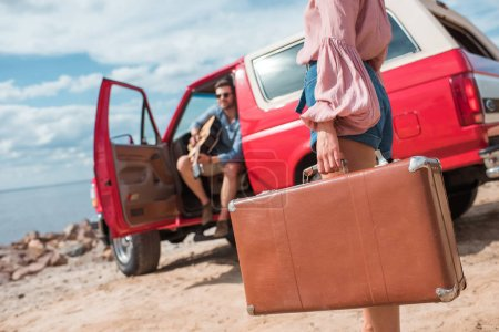 selective focus of girl with suitcase and boyfriend with guitar near red jeep on road trip
