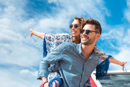 Photo for Happy man piggybacking his smiling girlfriend with blue sky on background - Royalty Free Image