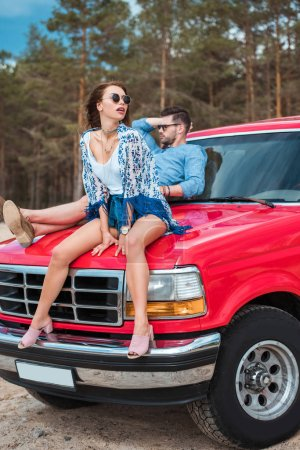 beautiful stylish couple sitting on red car on weekend