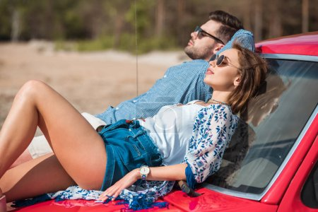beautiful young couple sunbathing together on red car