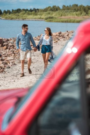 Photo for Selective focus of couple holding hands and walking on shore near the sea during road trip - Royalty Free Image