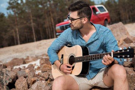 young man playing acoustic guitar outdoors, red jeep on background