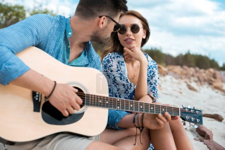 Photo for Male guitarist playing acoustic guitar and sitting with girlfriend outdoors - Royalty Free Image