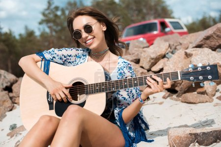 young smiling woman in sunglasses playing acoustic guitar outdoors