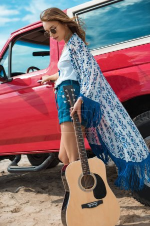 young woman with acoustic guitar posing near red car