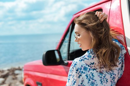 beautiful stylish woman at car during road trip near the sea