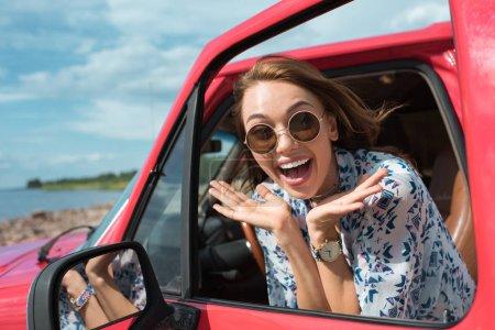 Foto de Chica atractiva muy contenta en gafas de sol de gesticular y en coche durante el viaje - Imagen libre de derechos