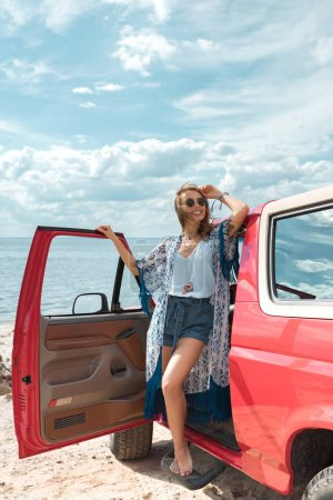 Photo for Happy young woman in sunglasses standing near red car - Royalty Free Image