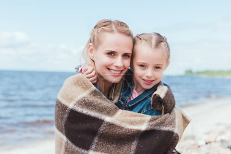 beautiful mother and daughter wrapped in blanket on sea shore
