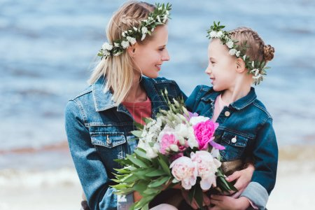 mother and daughter in floral wreaths with peony bouquet looking at each other on sea shore
