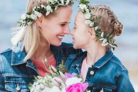 happy mother and daughter in floral wreaths touching noses